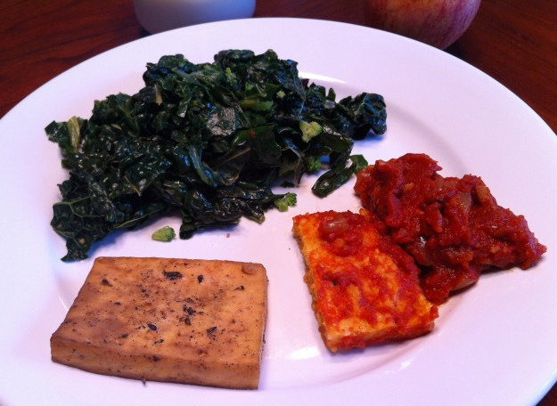 Braised kale with olives and walnuts, pan-fried tofu, and polenta with a tomato-onion ragout.  (And if you look closely, you can barely see the glass of almond milk and apple I paired with the items on the plate.)  So incredibly delish.