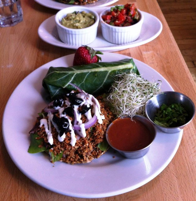 My friend and I split an order of flaxseed tostadas (the round item at the bottom of the photo) and a falafel wrap (the kale leaf log near the top of the plate).  I gave my friend my hot sauce (bottom center of the plate), cilantro (at the 3 o'clock spot on the plate), and sprouts (immediately to the left of the cilantro and to the top of the hot sauce) - but ate more than my fair share of the guacamole.  :)